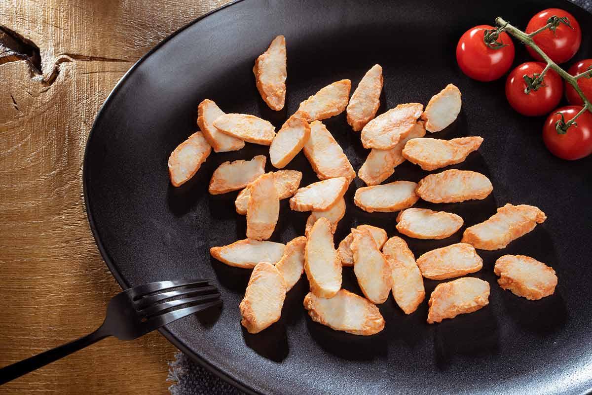 Hähnchenbrust, mariniert und gebraten, in Streifen, auf schwarzem Teller serviert, mit Besteck und etwas Beilage