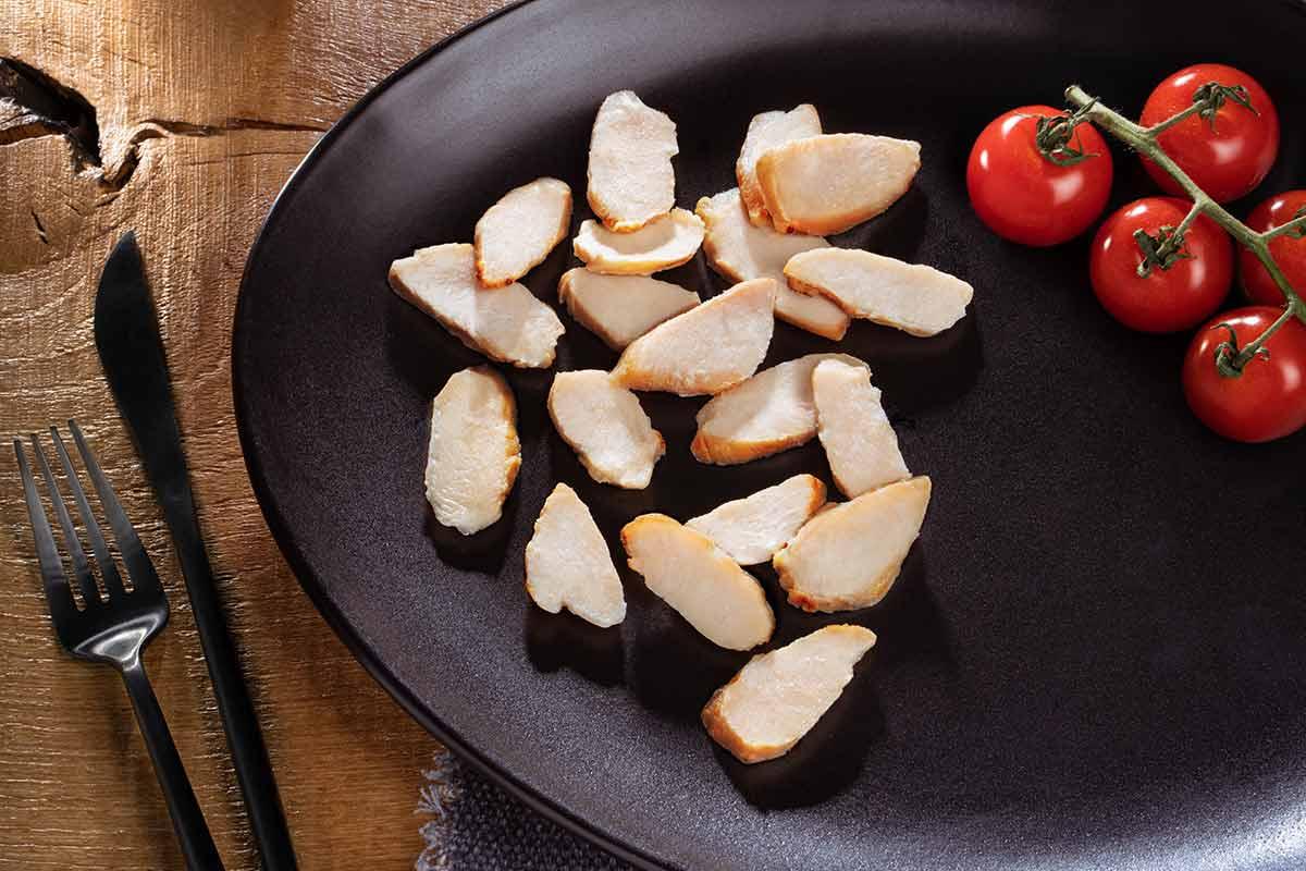 Hähnchenbrust, natur, in Streifen, auf schwarzem Teller serviert, mit Besteck und etwas Beilage
