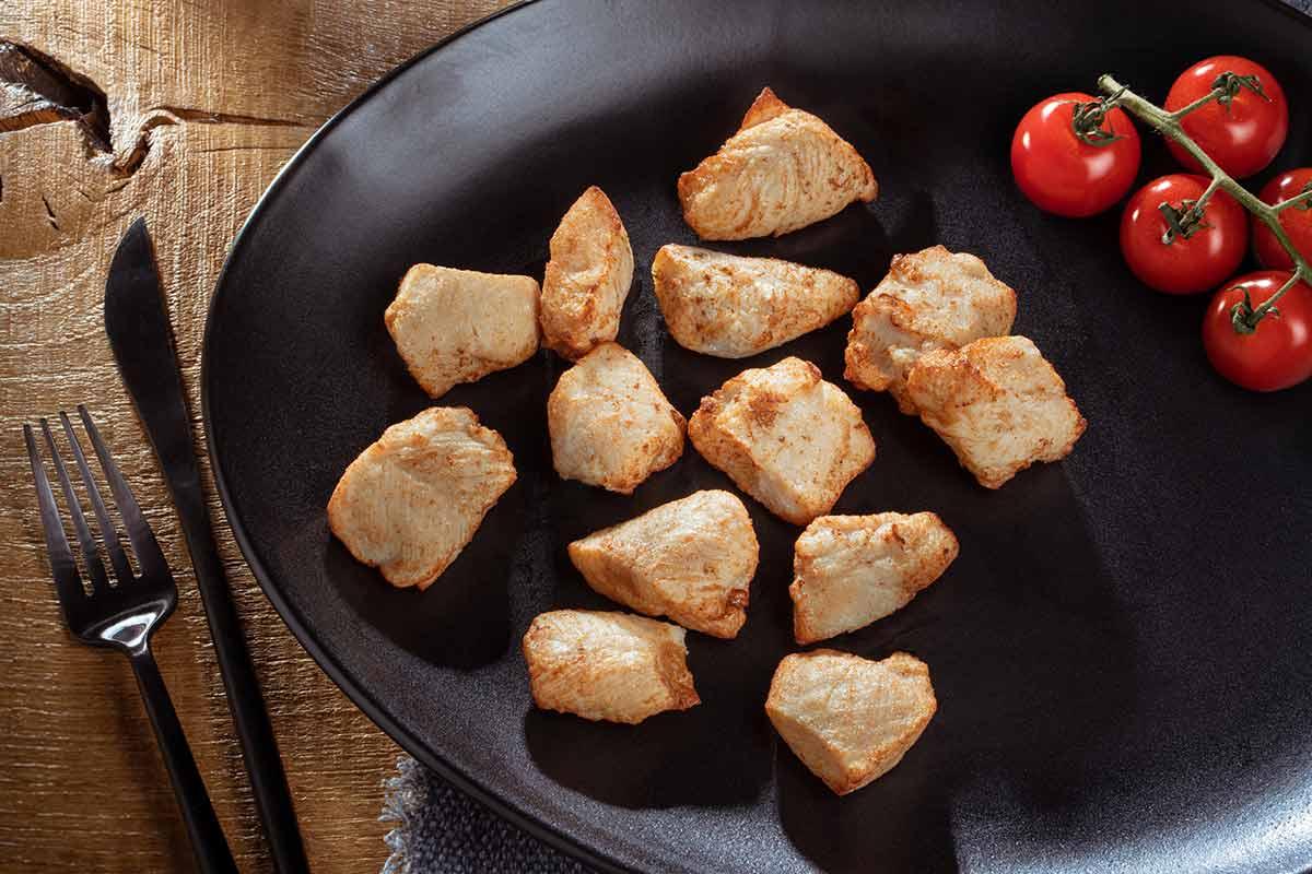 Hähnchenbrust Innenfiletstücke, gebraten, auf schwarzem Teller serviert, mit Besteck und etwas Beilage