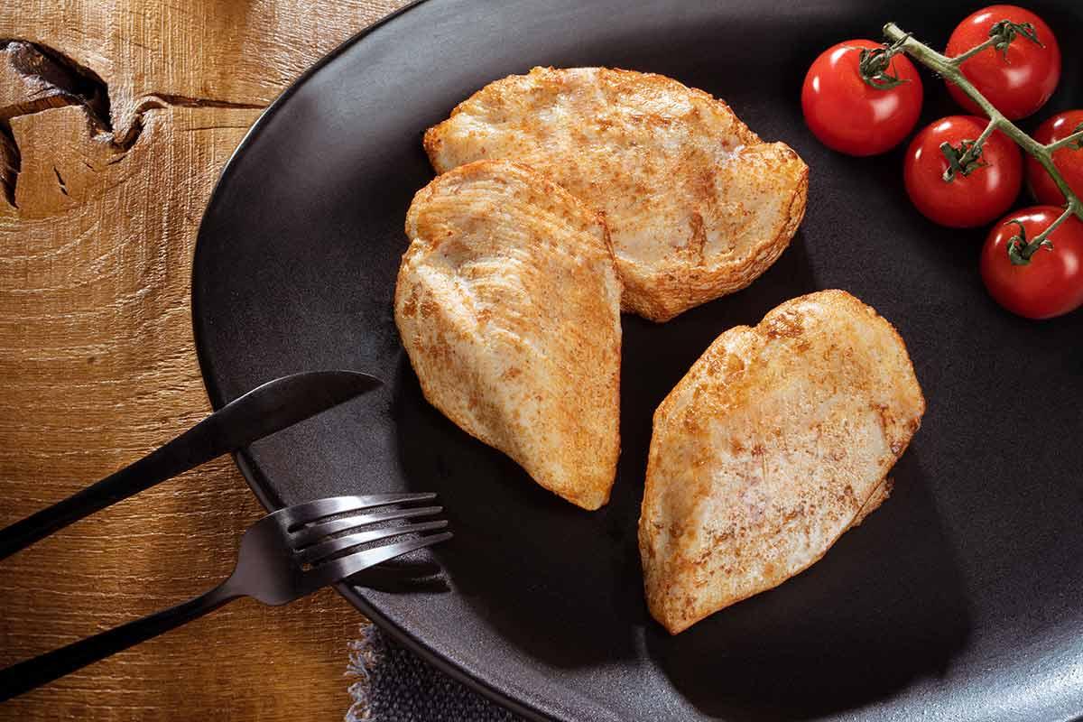Hähnchenbrustfilets, gebraten, auf schwarzem Teller serviert, mit Besteck und etwas Beilage