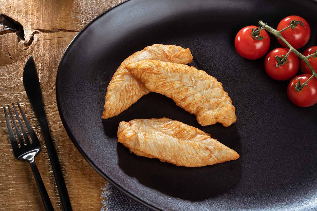 Hähncheninnenfiltes, gebraten, auf schwarzem Teller serviert, mit Besteck und etwas Beilage