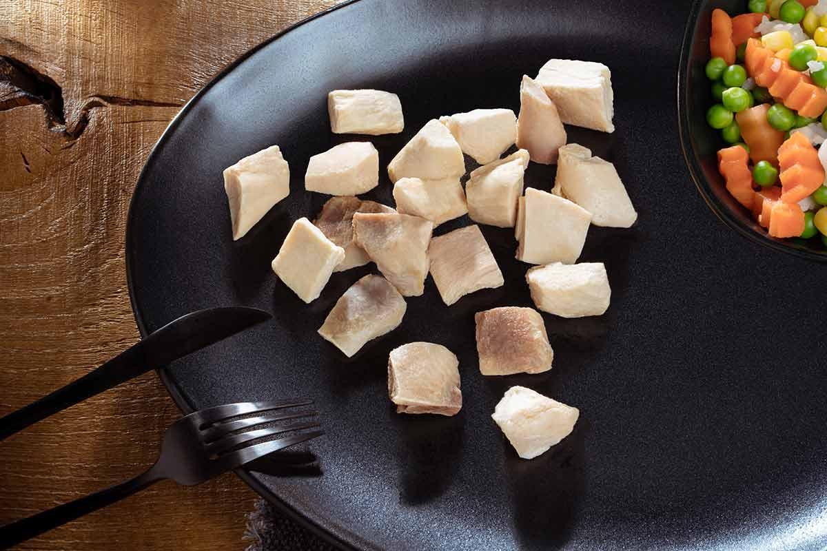 Hühnerfleisch, gegart und gewürfelt, auf schwarzem Teller serviert, mit Besteck und etwas Beilage