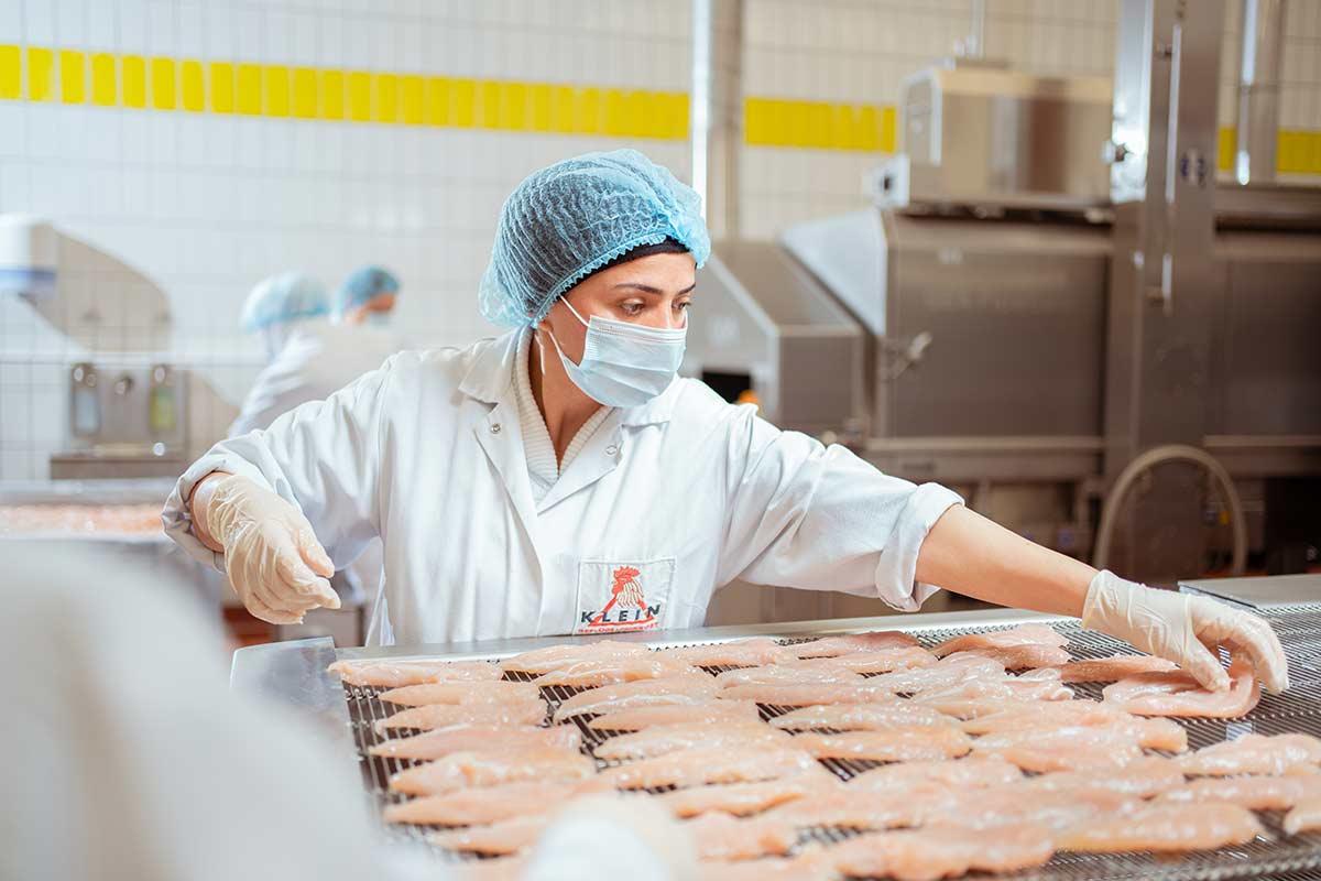 Mitarbeiterin an Bratstrasse legt Hähnchenfleisch auf Transportband